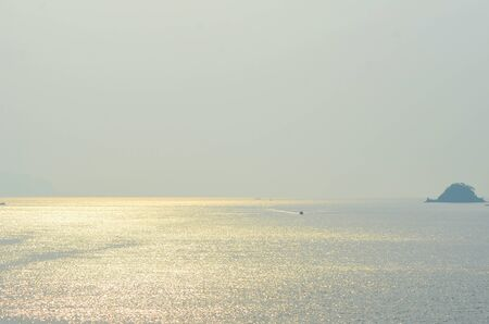 A small boat is dwarfed by a vast ocean. The water is golden and sparkling. A small tree covered is to one side, and a few other boata are visible. The golden horizon meets a hazy sky. Stock Photo