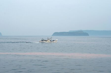 A white fishing trawler is heading past some islands. Parts of the ocean have turned pink from an algae bloom. The sky is clear but hazy. Stock Photo