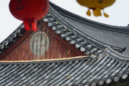 A close-up shot of the roof of a temple in Korea, showing ancient symbols. Stock Photo