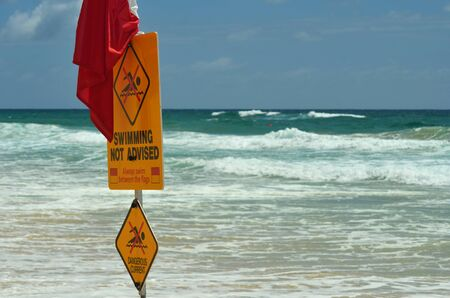 A yellow sign with a red flag is warning against swimming on a beach. Rough surf is the background and a surfer is just visible. The sky is blue with faint clouds.