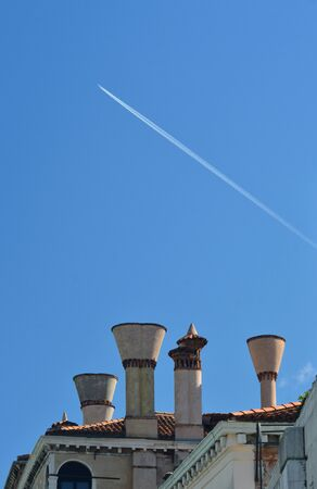 An airplane has left a white vapour trail in a clear blue sky. Below is a cluster of chimneys on a roof covered with terracotta tiles in Italy. Stock Photo