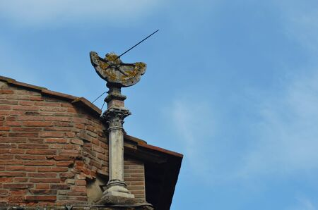 An old sundial is broken and covered in moss. It stands on the corner of a Tuscan house and rises above the roof. The sky is blue with white clouds