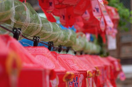 Red and green paper lanterns have been hung in rows in a temple to celebrate Buddha's birthday. Stock Photo