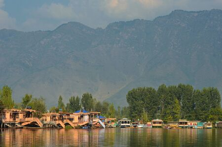 Wooden houseboats moored on Dal Lake in Kashmir. Their colours are reflected in the water. Trees line the shore, and mountains rise behind them to a cloudy sky.