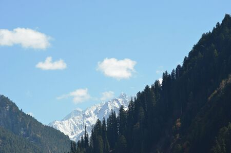 Dense forest covers mountains slopes which merge into higher peaks covered with snow. The sky is blue with white clouds.