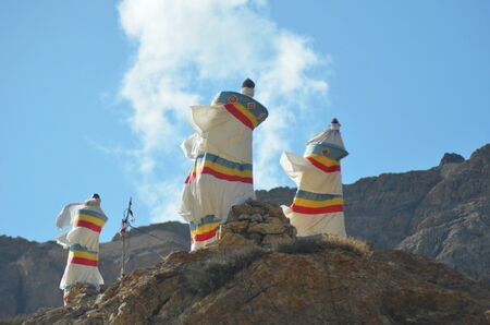 Three shrines made of white fabric rest on top of a rocky outcrop of barren hills in Ladakh. They have red, yellow and blue stripes, and are bending in the wind. The sky is blue with white clouds.