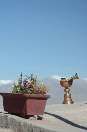 Two ceremonial cups of gold and bronze are resting on a stone ledge in a Buddhist temple. Beside them is a red planter box filled with flowers. In the distance are the snow topped peaks of teh Western Himalayas. The sky is blue. Stock Photo
