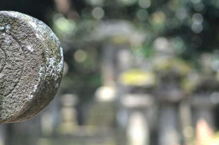 The round stone edging of a shrine in a Japanese temple is carved with concentric circles. The stone is weathered and covered in moss. Out-of-focus graves are in the background.
