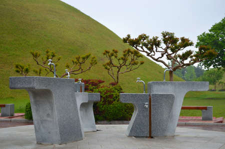 Water fountains made of concrete and with silver taps are at the base of a hill covered in grass. Small trees surround the drinking fountains. The sky is overcast.