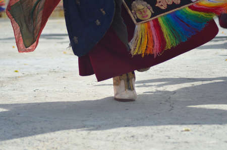 A monk is performing a dance in a Buddhist temple in Ladakh, India. Only his foot , shadow and the bottom of his robe are visible. His shoe is white leather with gold trim, while colourful fabrics adorn his red robe.