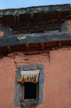Fabric flutters along the top of an open window in an old building. The wall has cracks and is terracotta in colour, with black eaves. The sky is blue.
