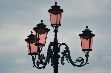 The famous pink lights of Venice. Four lamps with pink glass rest on an ornate black metal lamp post. The sky is overcast.