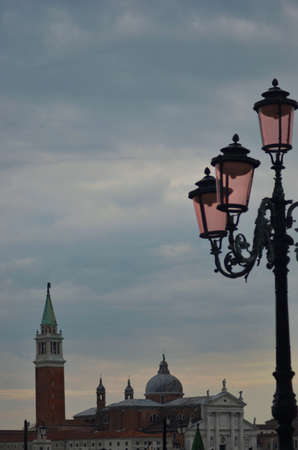 The evening sky in Venice is overcast, with grey clouds. The famous pink lanterns are in the foreground. The view looks across the lagoon (not visible) to the campanile of the Church of San Giorgio Maggiore.
