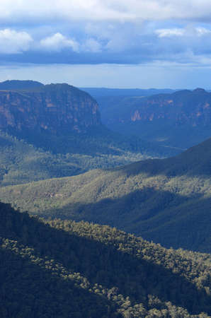 The forests of the Megalong Valley in the Blue Mountains, Australia, are bathed in sunlight. The distant mountains are in shadow. The sky is overcast. The distant mountains appear blue in colour.