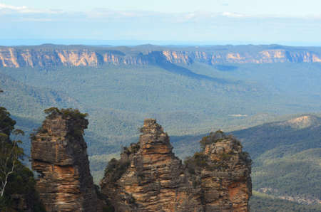 The Three Sisters, a group of rocks in the Blue Mountains in Australia, are seen against the Jamison Valley. Trees fill the valley, with rocky cliffs in the distance. The sky is cloudy.