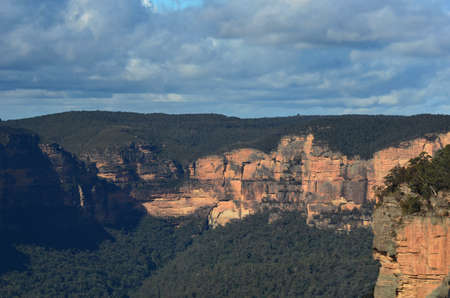 Sandstone cliffs are bathed in sunlight. They are surrounded by forest. The sky is overcast. They form part of the Megalong Valley in the Blue Mountains, Australia.