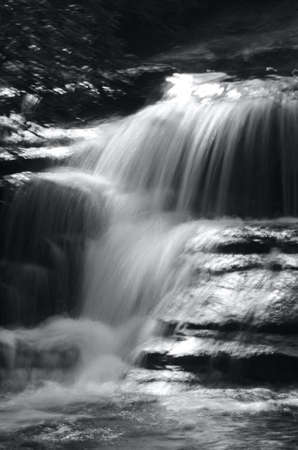 A river has formed a small waterfall over stones into a pond. A long exposure has made the water appear solid. Some bushes are to one side. The photograph is in black and white. Stock Photo