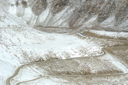 A road is dwarfed by snow covered mountains as it winds over a rocky slope. A white car and a road sign can barely be seen.