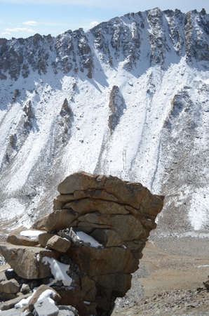 Some stones have been piled beside a mountain slope which is covered in snow. Patches of snow are also on the rocks. The surrounding landscape is rocky. The sky is blue.