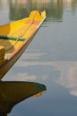 A bright yellow prow of a wooden boat has blue and green trim. It is reflected in the still waters of a lake. Reflections of clouds and buildings can also be seen.