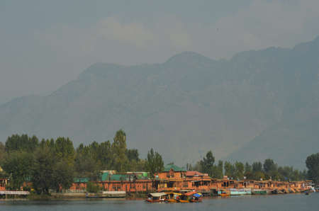 Wooden houseboats and other vessels are moored in Lake Dal, Srinagar, in Kashmir. Mountains rise in the distance. The sky is hazy.