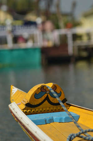 The bow of a bright yellow longboat with blue trim is seen against a backdrop of houseboats on Lake Dal, Kashmir. A rope runs from the prow and is coiled in the boat.