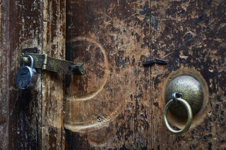 A round brass door handle is on an old door made of wood. The wood is marked and scratched, with signs of previous use. There is also a brass lock closed with a silver padlock. Stock Photo