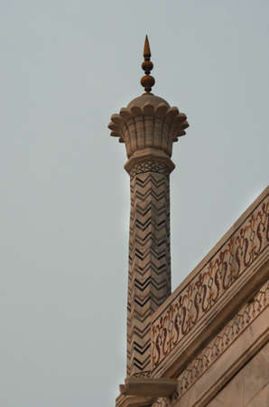 A marble pillar on the edge of the Taj Mahal is covered in geometric and flowing patterns. The marble appears a soft rose in colour under the dawn light.