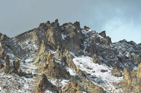 Rocks on a snow-covered mountain peak jut into an overcast sky. There has been a fall of snow. The landscape is barren with no vegetation. Stock Photo