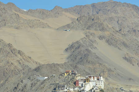 The white and red walls of the Buddhist Hemis Monastery near Leh in India contrast against the surrounding rocky mountains. An airforce plane is flying over the monastery. The sky is blue.