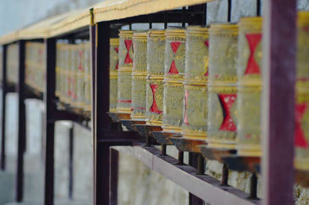 A double row of prayer wheels are supported by a wooden frame. They are red and faded yellow in colour. They are beside the wall of a Buddhist temple. Stock Photo