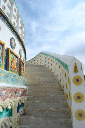 Stone stairs curve up between a brightly decorated balstrade and wall of a temple. Images of the Buddha plus other symbols contrast with the white paint. The sky is blue with white clouds, and a helicopter is just visible. Stock Photo