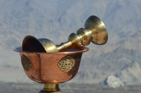 A golden cup used for offerings is resting inside a bronze Buddhist prayer bowl. The bowl has golden decoration. Rocky mountain slopes are in the background. Stock Photo