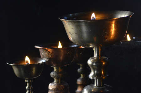 Old metal chalices are filled with oil and used as votive offerings. A flame is in each cup. Each cup is styled and decorated. The background is black.