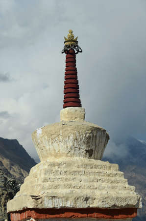 A stupa in India has a white stone base and dark red spire. The lotus and crescent moon on the top are gold in colour. The sky is filled with grey clouds. Mountains are in the background.