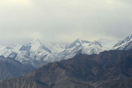 A mountain range, part of the Western Himalayas in Ladakh, India, is covered in snow. The sky is filled with snow clouds. A lower rocky mountain slope is in the foreground.