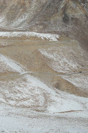 Patches of snow cover a rocky mountain slope in Ladakh, India. A road winds across it. A truck is just visible, dwarfed by the size of the mountain. Stock Photo
