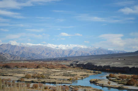 A river runs through a valley in Ladakh, India, past some trees, shrubs and a few houses. The foothills of the Himalayas are in the distance, the higher mountains covered with snow. The sky is blue