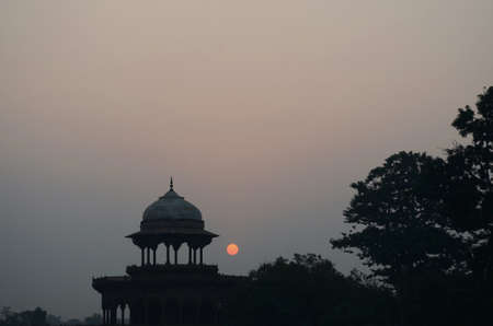 The orange ball of the rising sun is seen beside the marble dome of a pavillion in the grounds of the Taj Mahal, India. Trees are to one side. Some birds are just visible against the colours of sunrise.