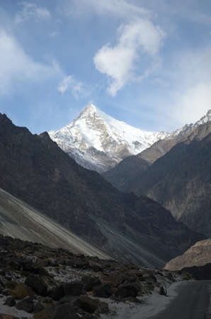 A valley between rocky mountain slopes ends at a mountain peak covered in snow. It forms part of the Western Himalayas. A road is in the foreground, and the sky is blue with white clouds.