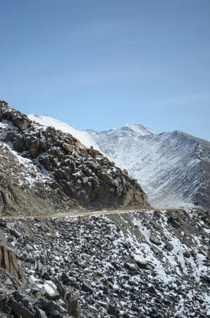 A highway climbing towards the Khardung-La Pass in India is dwarfed by the size of the mountains. Snow covers distant peaks and the sky is blue. Stock Photo