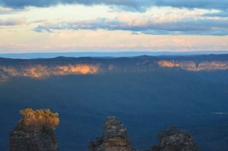 Sunset is breaking through the clouds to touch the top of the tallest Three Sisters in the Blue Mountains, Australia and the top of  distant mountain range. Below is a forest filled valley.