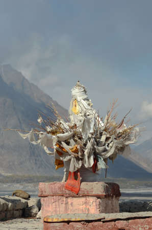 An offering of twigs and Buddhist prayer flags sits on a shrine. Behind are some mountains, part of the Western Himalayas in Ladakh, India. The sky is overcast.