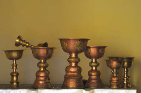Golden cups used in Buddhist religious ceremonies standing on a shelf in a temple. Some are plain, while others carved details. The wall behind is dark yellow, giving the photo golden tones.