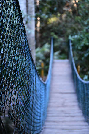 A wooden suspension footbridge has dark metal mesh railings. The focus is on the foreground, with the end of the bridge leading into a forest out of focus.
