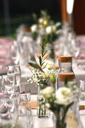 Tables are set with pink napkins, wine glasses and vases with white flowers for a wedding. The focus is on the foreground, with distant tables out of focus.