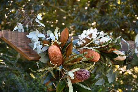 Banksia and other native Australian flowers and leaves have been tied to a wooden frame as part of an outdoors wedding decoration. Trees are in the background.