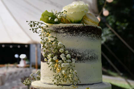 White gypsophila (or baby's breath) and white roses decorate the top tier of a white and chocolate wedding cake. A cream macaroon with yellow filling is among the flowers.
