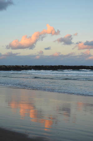 Clouds tinged pink from the sunset are reflected in the waters of a beach. A rock break-wall, or groyne, is in the distance.