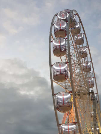 The cabins of a ferris-wheel have been lit up for evening. they are seen from below, against white and grey clouds.